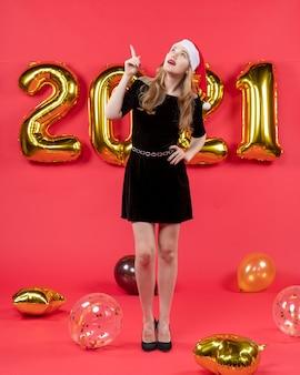 Vista frontal jovem de vestido preto apontando para balões de teto em vermelho