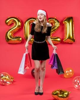 Vista frontal jovem de vestido preto segurando balões coloridos de sacolas de compras em vermelho