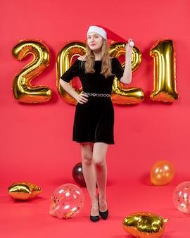 Vista frontal jovem de vestido preto segurando balões de chapéu de natal em vermelho