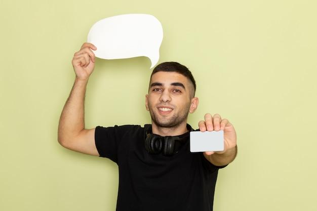 Vista frontal jovem do sexo masculino com camiseta preta segurando uma placa branca e um cartão verde