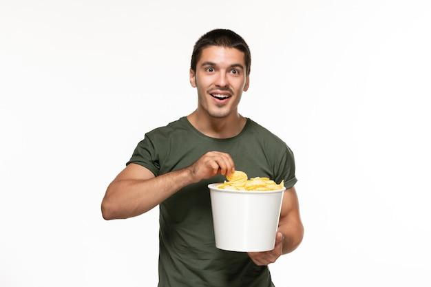 Vista frontal jovem do sexo masculino com camiseta verde segurando a cesta com batatas cips na superfície branca clara filme solitário filme de prazer