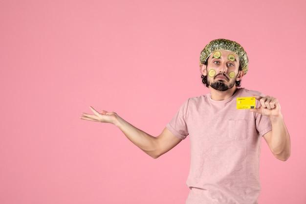 Vista frontal jovem do sexo masculino com máscara no rosto, segurando o cartão do banco no fundo rosa