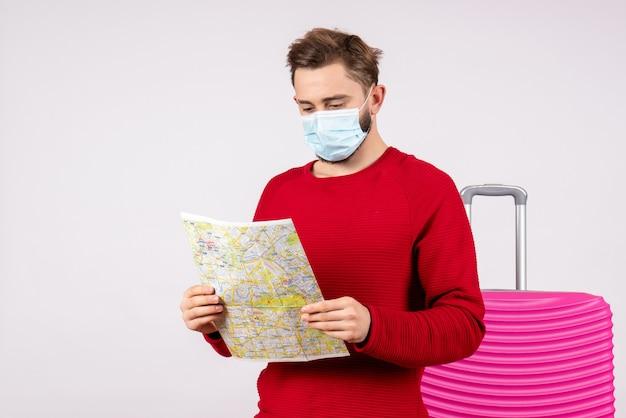 Vista frontal jovem do sexo masculino com máscara segurando o mapa na parede branca vírus voyage covid- vôo viagem férias cor