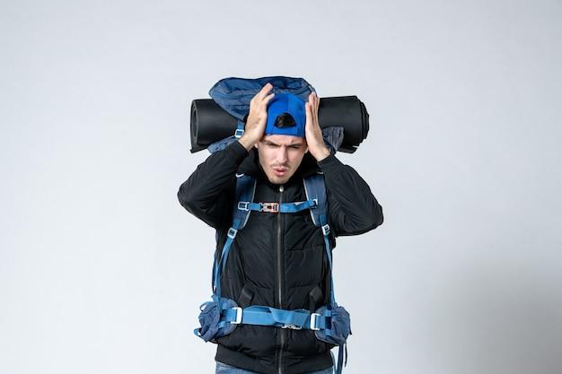 Vista frontal jovem do sexo masculino com mochila indo em caminhadas no fundo branco campanha tenda ar natureza altura floresta montanha céu