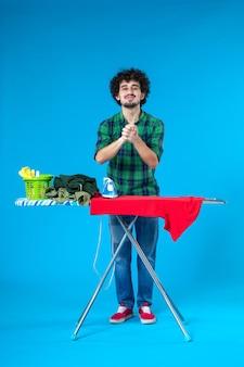 Vista frontal jovem do sexo masculino com tábua de engomar no fundo azul humano lavando trabalhos domésticos cor limpa casa