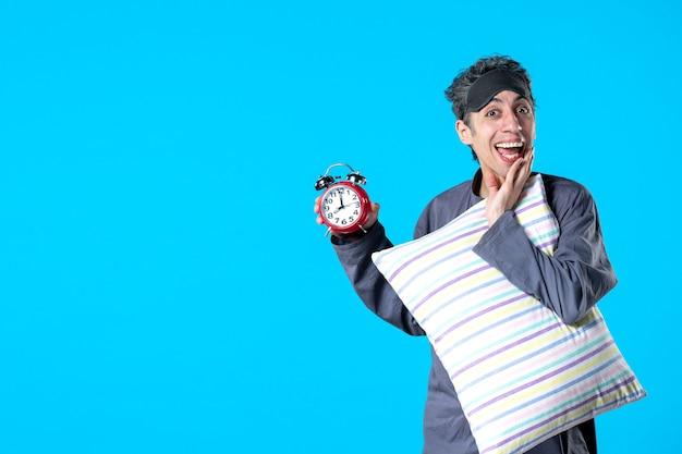 Vista frontal jovem do sexo masculino de pijama segurando travesseiro e relógios no fundo azul quarto escuro insônia cama à noite sono tarde sono descanso sonho