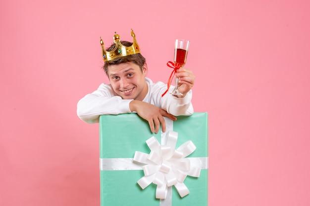 Vista frontal jovem do sexo masculino dentro de presente com coroa e copo de vinho no fundo rosa