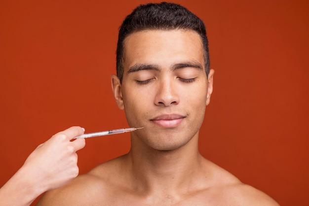 Vista frontal jovem do sexo masculino e seringa