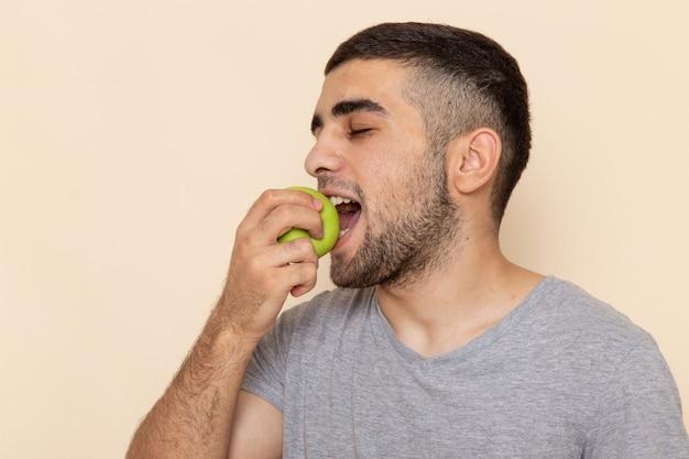 Vista frontal jovem do sexo masculino em camiseta cinza e jeans azul mordendo maçã em bege