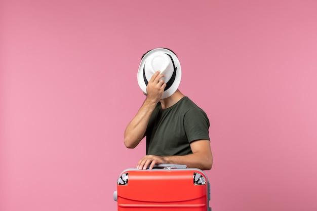Vista frontal jovem do sexo masculino em férias segurando seu chapéu no chão rosa viagem homem mar viagem viagem férias