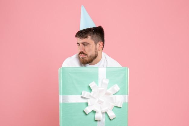 Vista frontal jovem do sexo masculino em pé dentro da caixa de presente na cor rosa pijama festa foto emoção sono humano