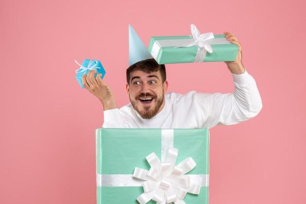 Vista frontal jovem do sexo masculino em pé dentro da caixa de presente na cor rosa pijama festa foto emoção sono natal