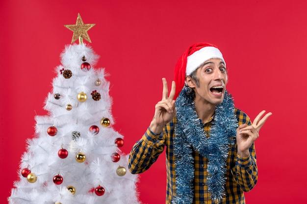 Vista frontal jovem do sexo masculino em torno da atmosfera de ano novo na parede vermelha emoção feriados natal