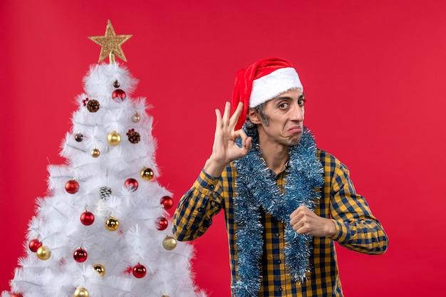 Vista frontal jovem do sexo masculino em torno da atmosfera de ano novo na parede vermelha feriado de natal