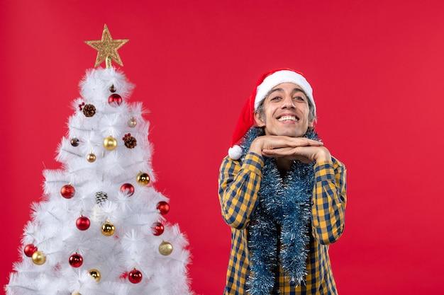 Vista frontal jovem do sexo masculino em torno da atmosfera de ano novo na parede vermelha, férias natalinas