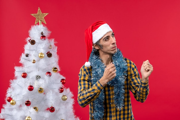 Vista frontal jovem do sexo masculino em torno da atmosfera de ano novo nas cores da parede vermelha feriado natal