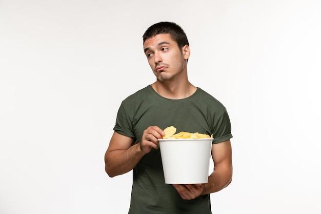 Vista frontal jovem do sexo masculino em uma camiseta verde com batata cips assistindo filme na parede branca clara pessoa masculino filme solitário cinema