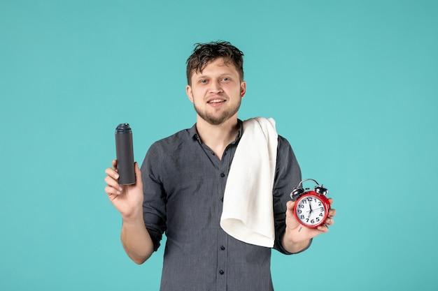 Vista frontal jovem do sexo masculino segurando um relógio no fundo azul
