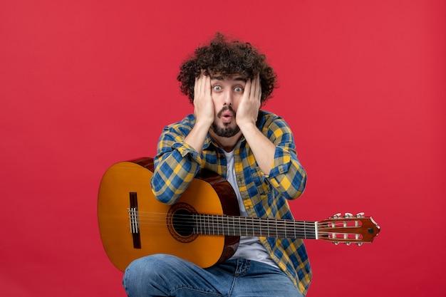 Vista frontal jovem do sexo masculino sentado com a guitarra na parede vermelha aplausos banda concerto músico música cor ao vivo