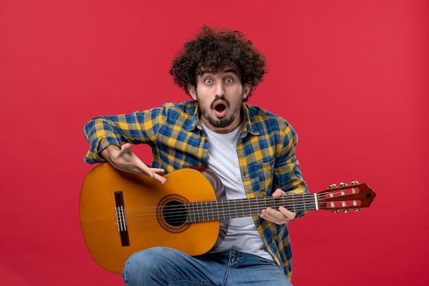 Vista frontal jovem do sexo masculino sentado com guitarra na parede vermelha tocar música concerto cor músico aplausos banda ao vivo