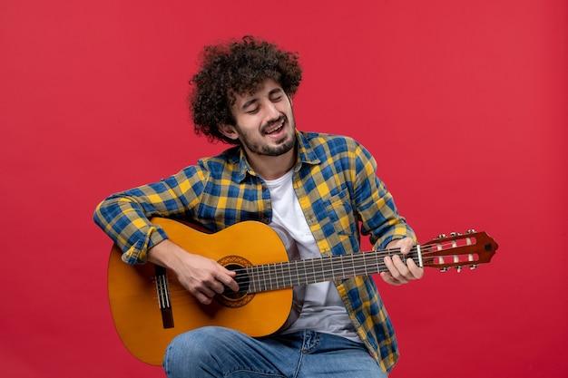 Vista frontal jovem do sexo masculino sentado e tocando guitarra na parede vermelha concerto ao vivo cor músico aplausos banda tocar música