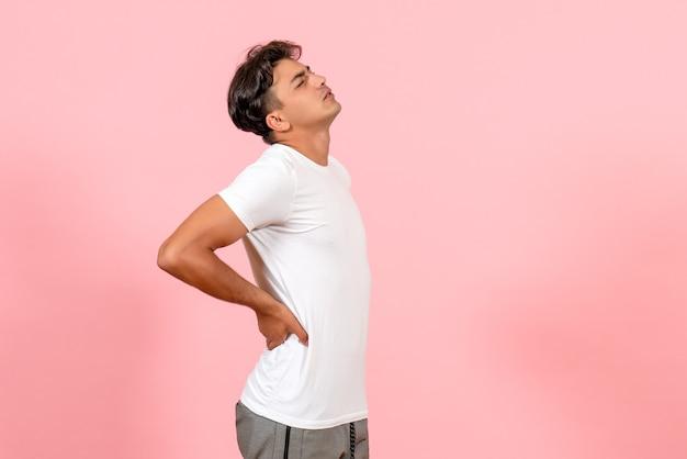Vista frontal jovem do sexo masculino tendo dor nas costas na cor de fundo rosa modelo emoção masculino