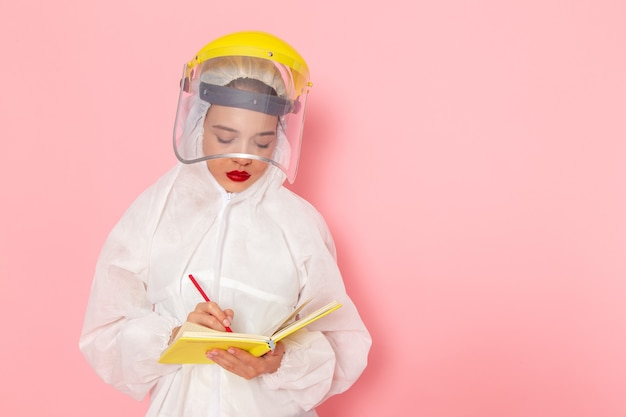 Vista frontal, jovem e bela mulher em um terno branco especial, usando um capacete protetor, escrevendo notas sobre a mulher do traje espacial rosa