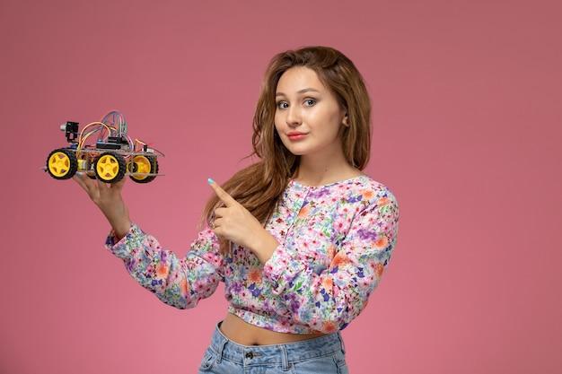 Vista frontal, jovem e bela mulher em uma camisa com design flor e calça jeans segurando um carrinho de brinquedo no fundo rosa