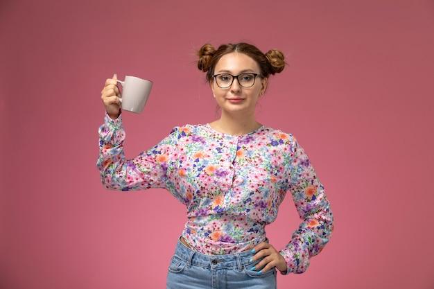 Vista frontal, jovem e bela mulher em uma camisa com design flor e calça jeans, segurando um copo no fundo rosa