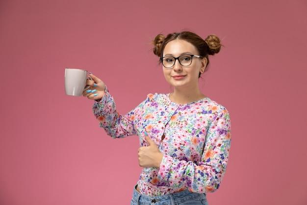Vista frontal, jovem e bela mulher em uma camisa com design flor e jeans azul, segurando a xícara e sorrindo no fundo rosa