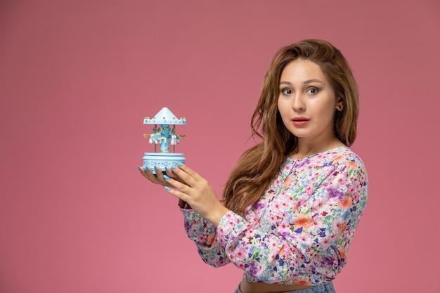 Vista frontal, jovem e bela mulher em uma camisa com design floral e jeans azul segurando uma lembrança no fundo rosa