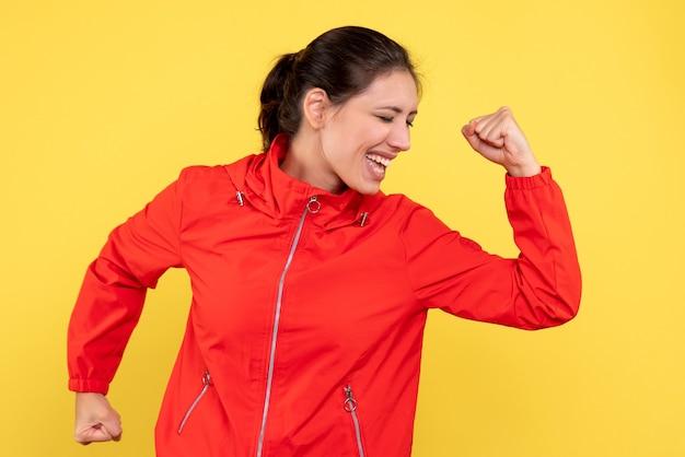Vista frontal, jovem e bonita mulher com casaco vermelho sobre fundo amarelo