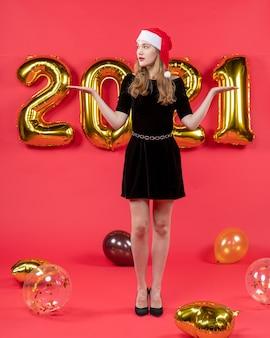 Vista frontal, jovem e bonita mulher de vestido preto abrindo balões de mãos no vermelho