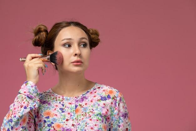 Vista frontal, jovem e linda mulher em uma camisa com design floral e jeans azul fazendo maquiagem no fundo rosa