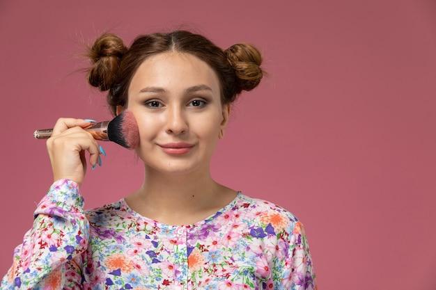 Vista frontal, jovem e linda mulher em uma camisa com design floral e jeans azul fazendo uma maquiagem com um leve sorriso no fundo rosa