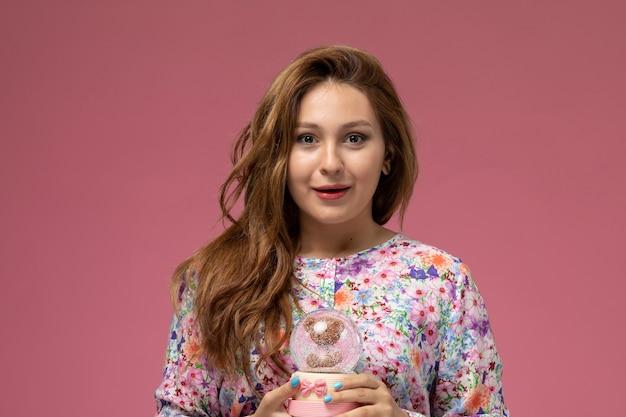 Vista frontal, jovem e linda mulher em uma camisa com design floral e jeans azul segurando um pequeno brinquedo de vidro sorrindo no fundo rosa