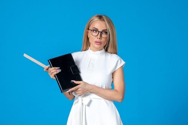 Vista frontal jovem empresária em lindo vestido branco com bloco de notas azul