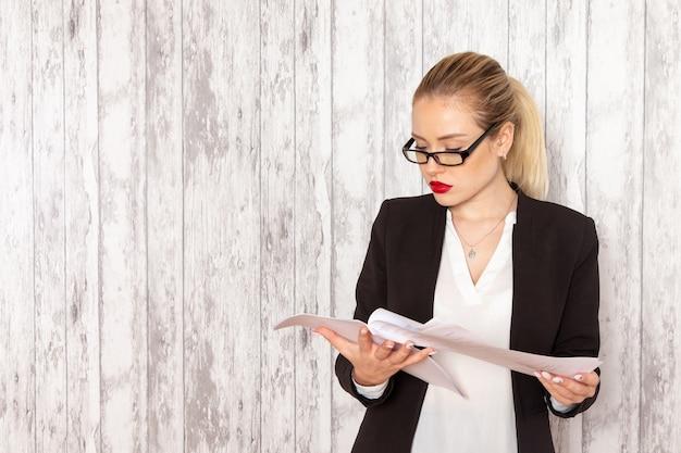 Vista frontal jovem empresária em roupas estritas jaqueta preta lendo documento na superfície branca