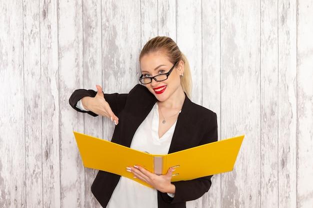 Vista frontal jovem empresária em roupas estritas, jaqueta preta segurando arquivos e documentos com um sorriso na superfície branca