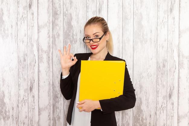 Vista frontal jovem empresária em roupas estritas, jaqueta preta segurando arquivos e documentos na mesa branca
