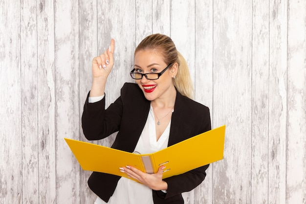 Vista frontal jovem empresária em roupas estritas, jaqueta preta segurando arquivos e documentos sorrindo em uma superfície branca.