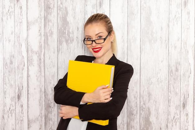 Vista frontal jovem empresária em roupas estritas, jaqueta preta segurando arquivos e documentos sorrindo na superfície branca