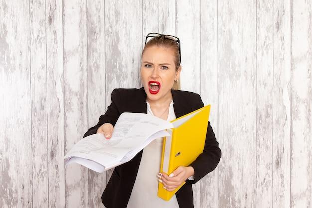 Vista frontal jovem empresária em roupas estritas, jaqueta preta segurando arquivos na superfície branca