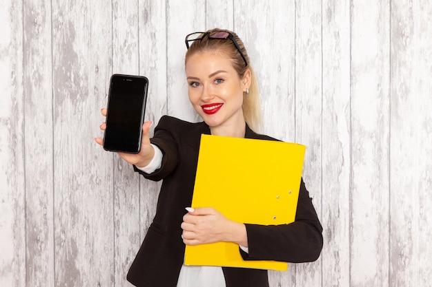 Vista frontal jovem empresária em roupas estritas, jaqueta preta segurando documentos e telefone na superfície branca