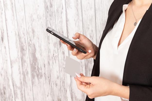 Vista frontal jovem empresária em roupas estritas, jaqueta preta segurando o cartão e o telefone na superfície branca.