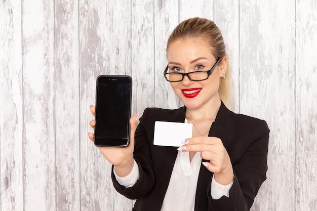 Vista frontal jovem empresária em roupas estritas, jaqueta preta segurando o cartão e o telefone na superfície branca