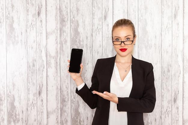 Vista frontal jovem empresária em roupas estritas, jaqueta preta segurando o telefone na superfície branca.