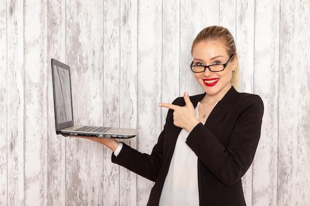 Vista frontal jovem empresária em roupas estritas jaqueta preta usando seu laptop com sorriso na parede branca trabalho trabalho escritório negócio trabalhador feminino
