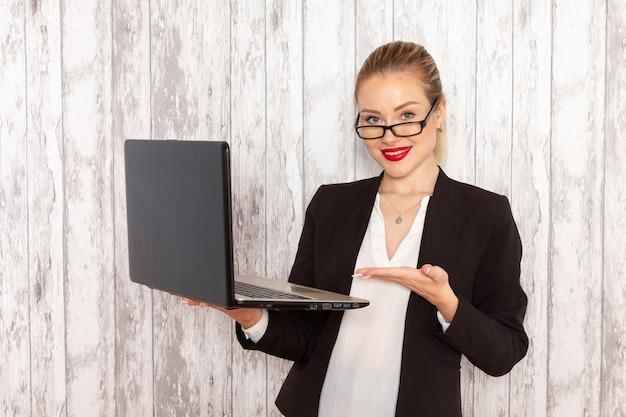 Vista frontal jovem empresária em roupas estritas, jaqueta preta usando seu laptop com um leve sorriso na parede branca trabalho trabalho escritório negócios trabalhador feminino