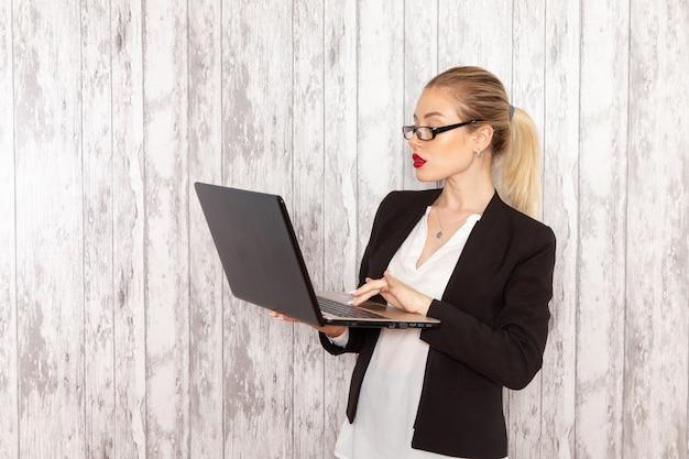 Vista frontal jovem empresária em roupas estritas, jaqueta preta usando seu laptop na superfície branca
